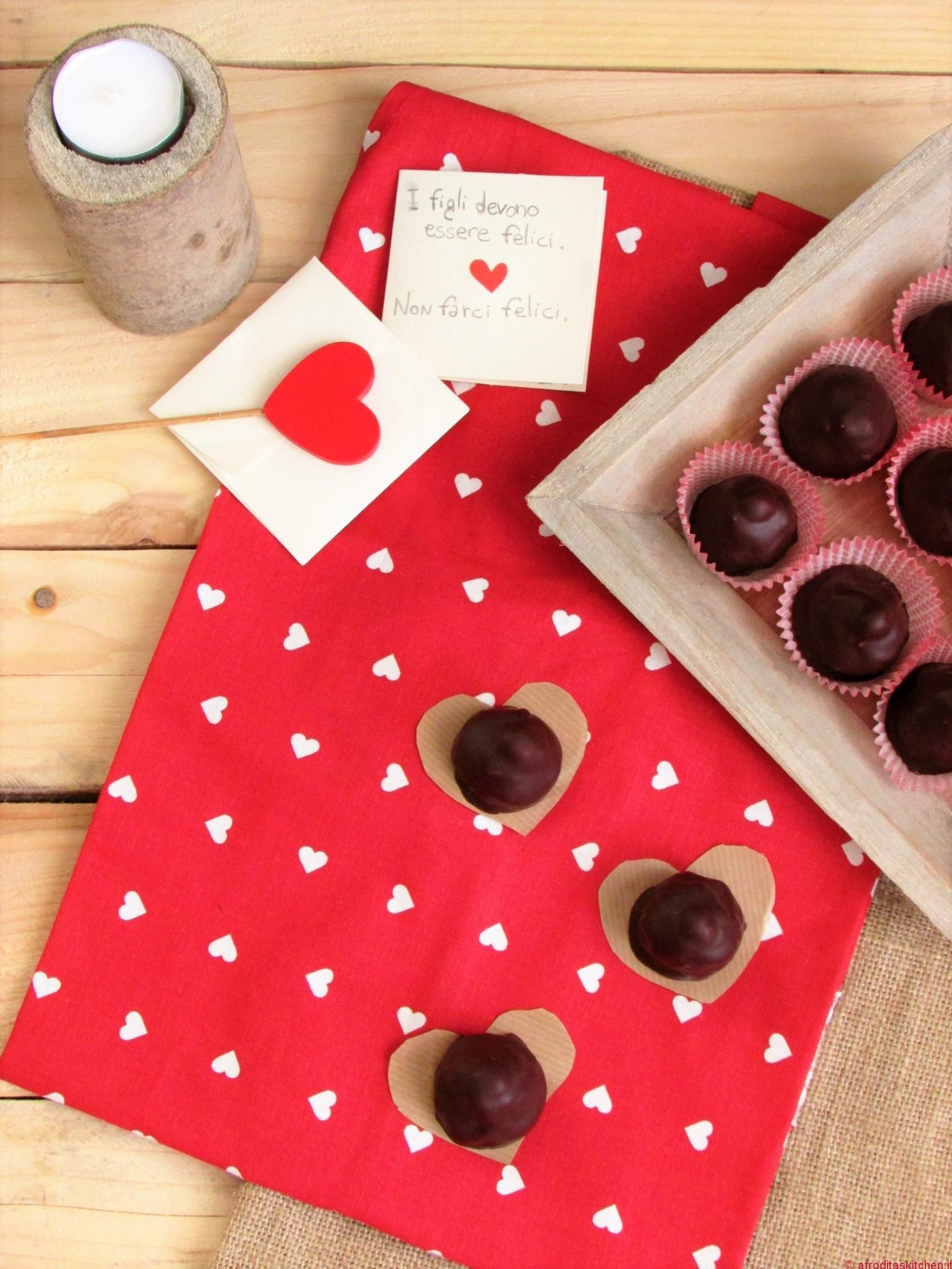 Baci al cioccolato fondente con cuore morbido al cioccolato bianco, pepe rosa e mirtilli rossi